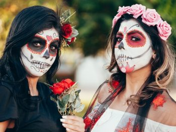 Two young women with sugar skull makeup - a typical Day of the Dead Traditions