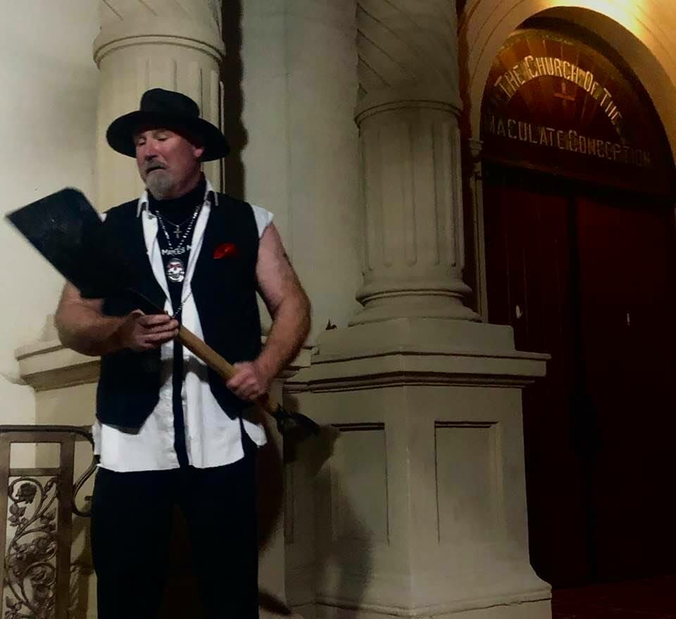 Guide of the ghost tour old town wearing black pants and black vest with white shirt