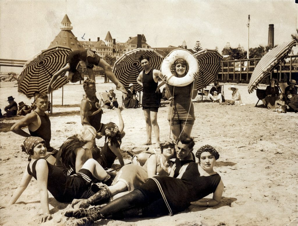 historic picture in sepia with ladies in the 20s in swimsuits on the beach at the hotel del coronado