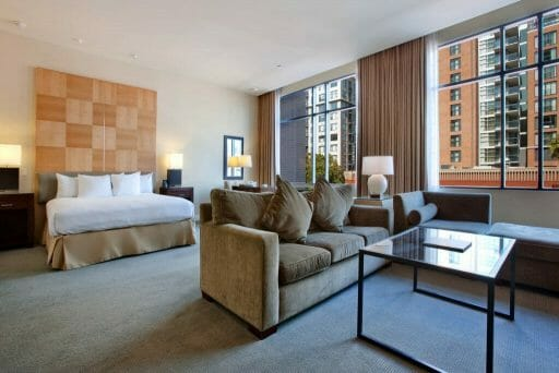 Hotel room at the Hilton Gaslamp San Diego with bed, two couches, table and large window front looking at urban scene