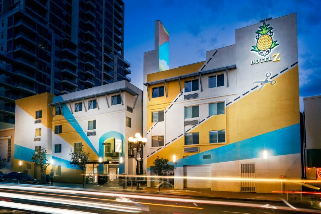 Outside photo of Hotel Z during blue hour. White Facade with yellow and turquoise strips painted on facade