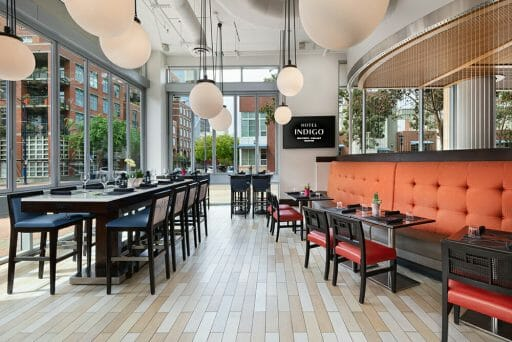 Restaurant at Hotel Indigo - Dark wood tables and chairs, orange accent wall and large white globe chandeliers
