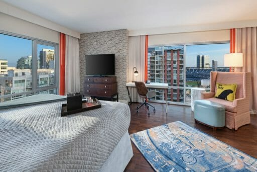Hotel Room at Hotel Indigo with bed, recliner and two large windows looking out at Petco Park