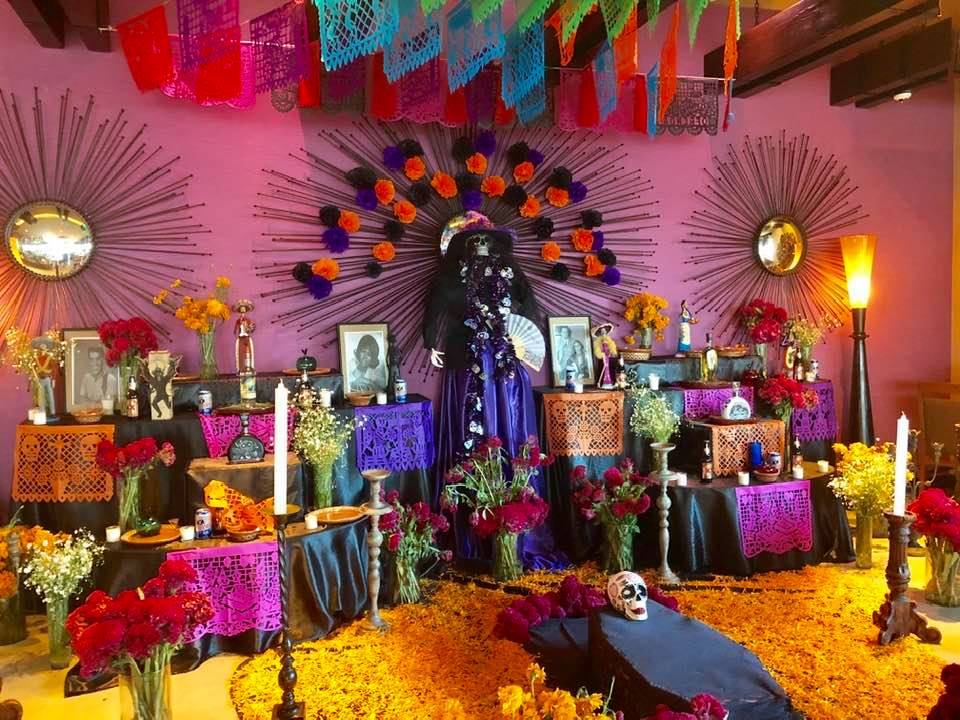 Traditional alter for day of the dead with colorful decorations, photos of the dead, flowers, decoration, favorite foods, and candles