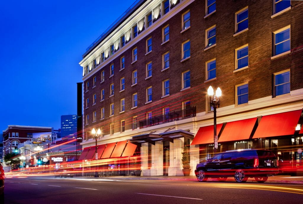 Long exposure photo of Andaz hotel during blue hour. Brick building with white trim and red sun shades on the first floor