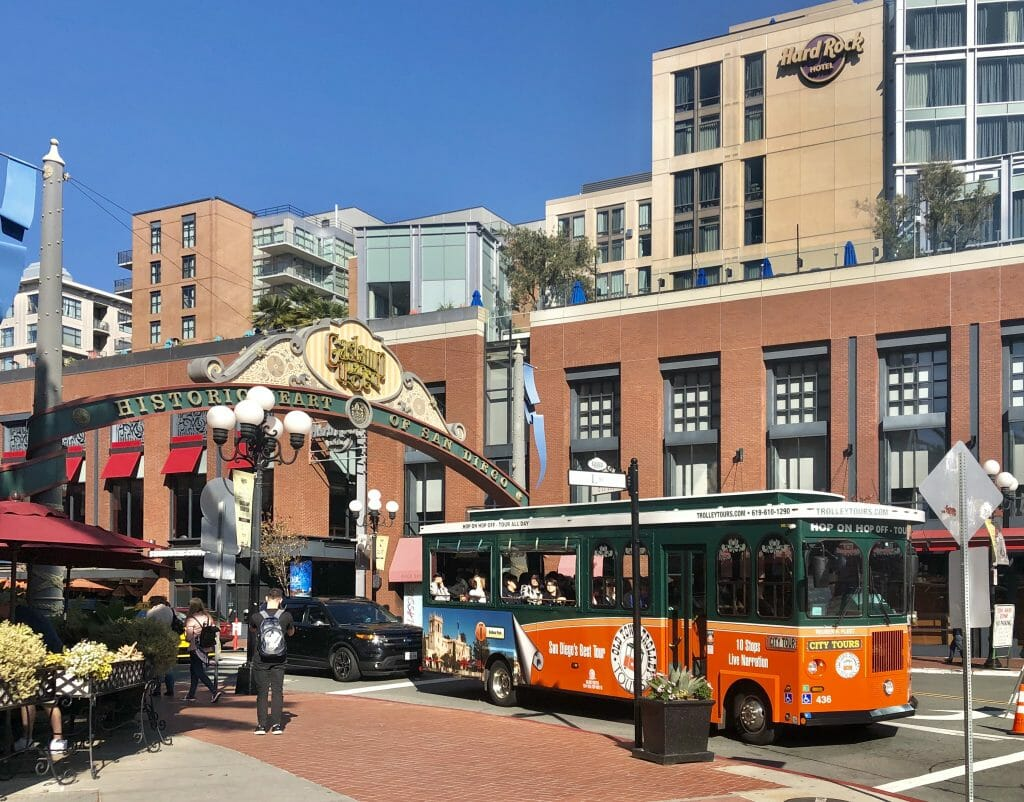 Entrance to Historic Gaslamp Quarter with red historic trolley city tour bus in the foreground and the San Diego Hard Rock Hotel in the background