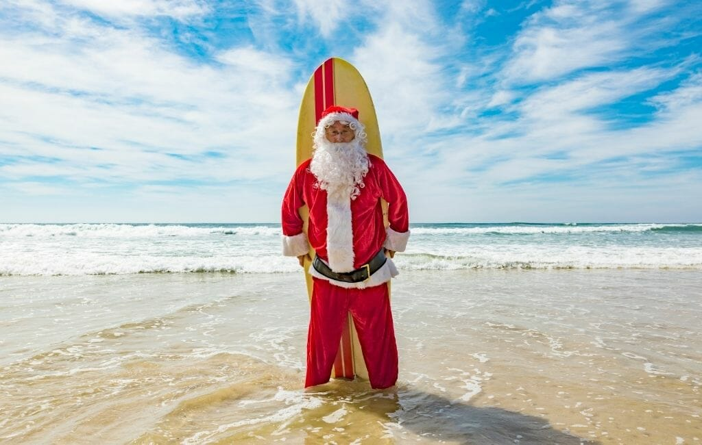 Man in Santa Clause Costume standing on the beach with surfboard behind him on a sunny day