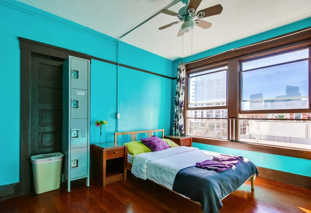 Room at Hostel in San Diego - Bright turquoise walls and two large windows looking out at downtown