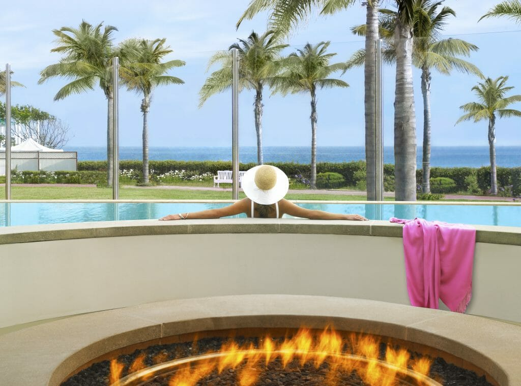 Gas firepit in the foreground. Woman sitting in pool  with white hat, palm trees and Pacific Ocean in the background - Coronado Island Hotels - Hotel Del Coronado