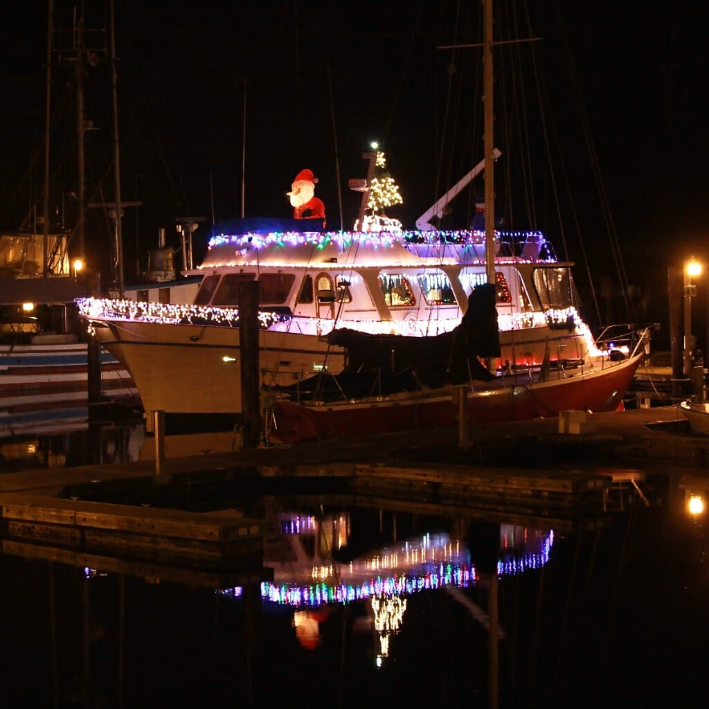 Boat on dock decorated with Christmas lights and Santa Claus