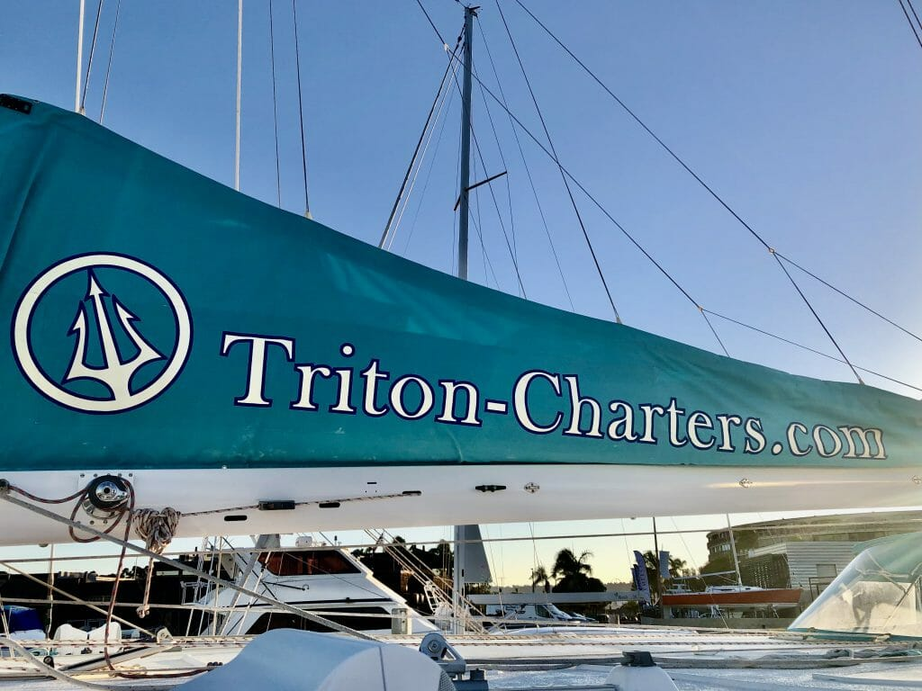 Teal sail with white writing: Triton Charter - San Diego Catamaran Cruise