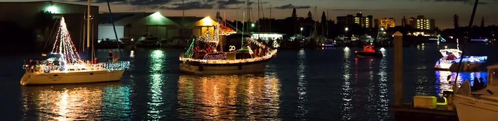 Boats decorated with Christmas lights passing through a channel