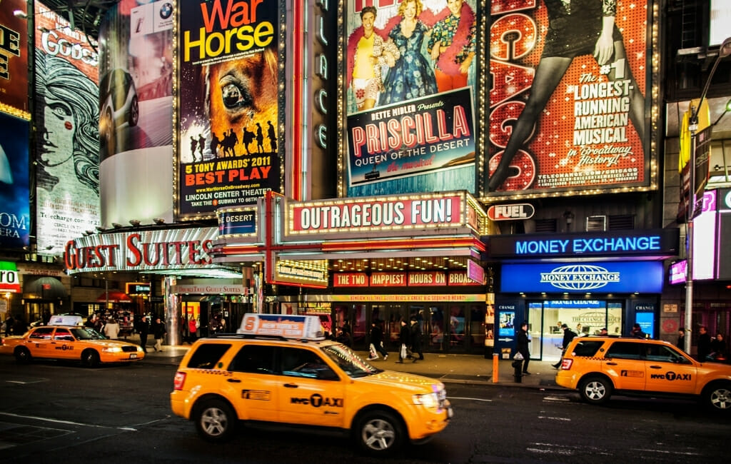 Broadway New York City with Advertisement for plays and yellow cabs in the street in front