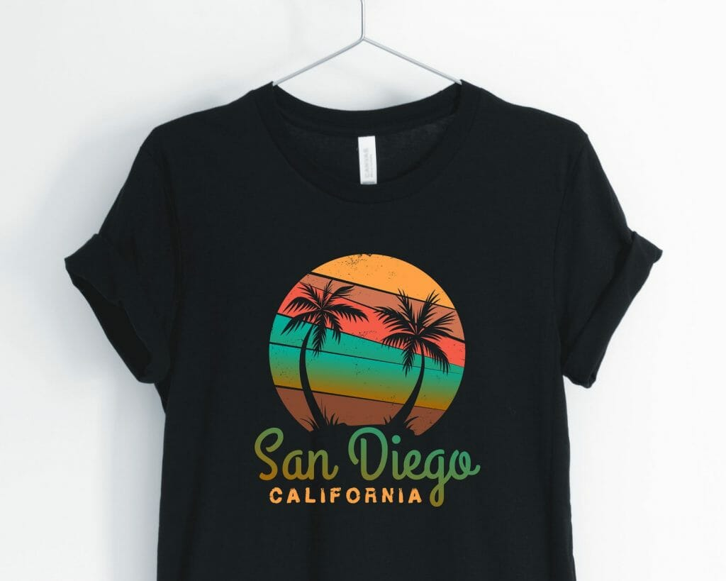 Black tshirt with vintage san Diego print: San Diego California Text and above a colorful circle with yellow red and green with black palm tree outlies