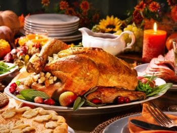 Festive holiday table with Turkey, side dishes, candles, orange candles - Thanksgiving dinner in San Diego