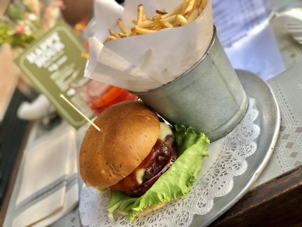 Burger on a metal plate with a metal bucket full of fries
