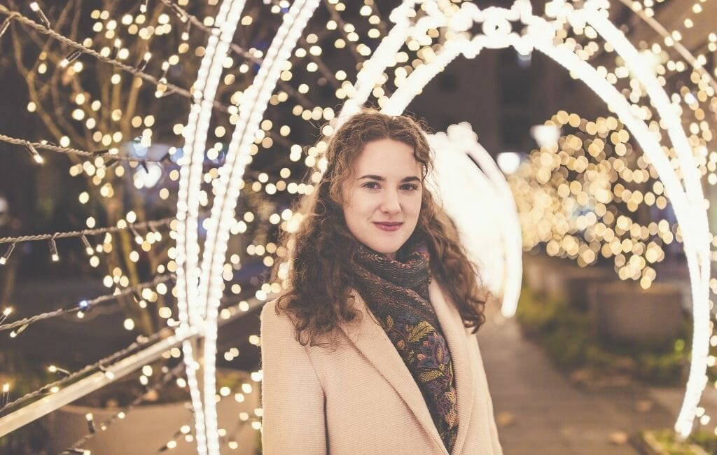 Woman standing in Holiday lights tunnel