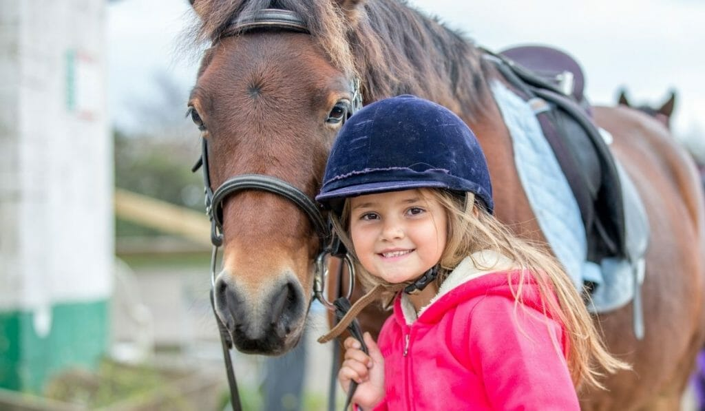 Young girl with riding helmet and pink jacket leading a horse, smiling into the camera