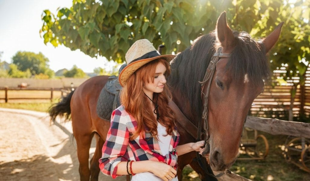 Red haired woman leading a brown horse on a horse farm