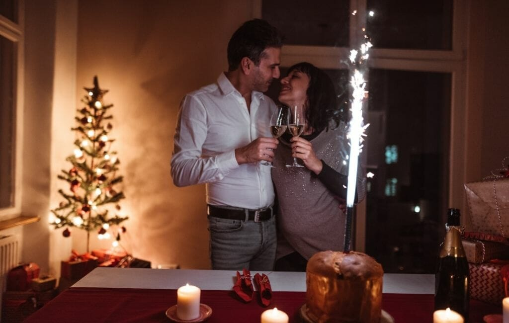 Couple toasting with champagne with cake decorated with firework sparkles and christmas tree in the background