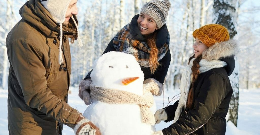Family with one kid building a snow man in a wintery landscape