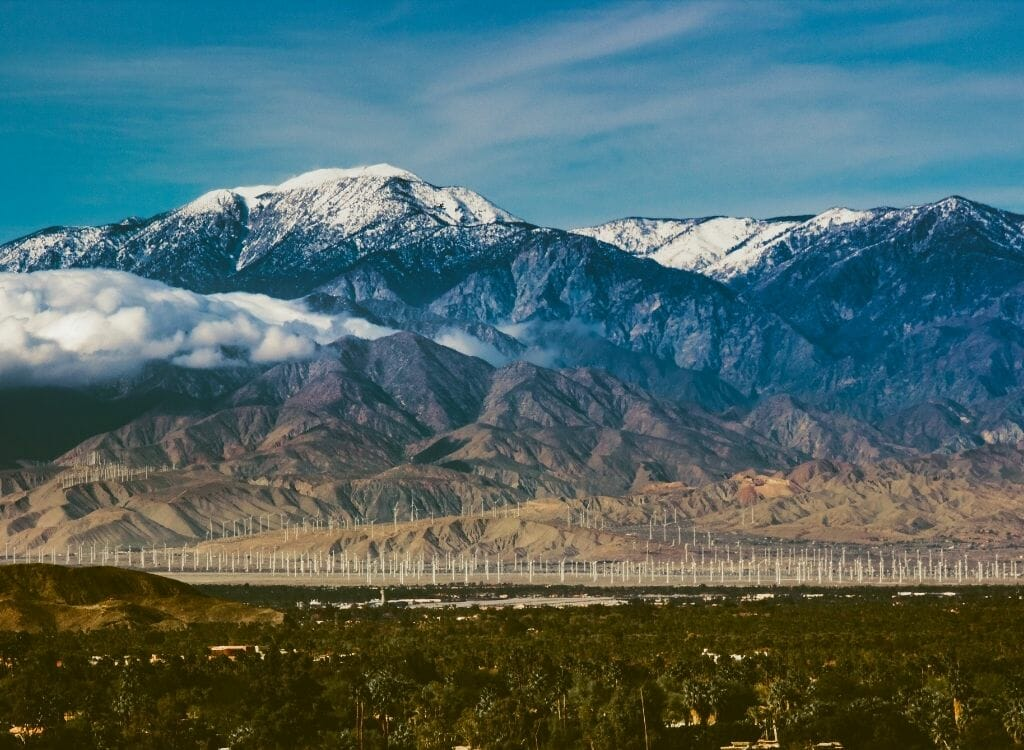 Winter landscape with brown fields in the foreground and snowcapped Sierra Nevada mountains in the background - Snow in Southern California Mt San Jacinto