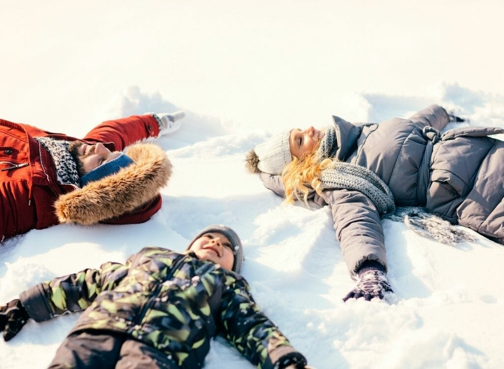Two adults (man and woman) and a child lying in the snow making snow angels