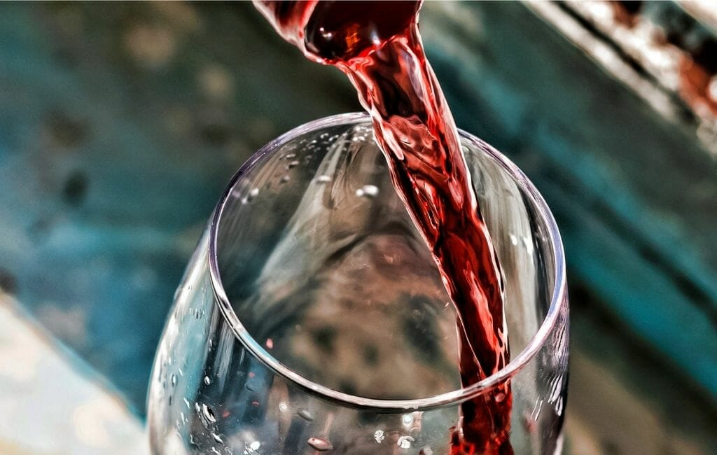 closeup of a wine glass and bottle top pouring red wine into glass -