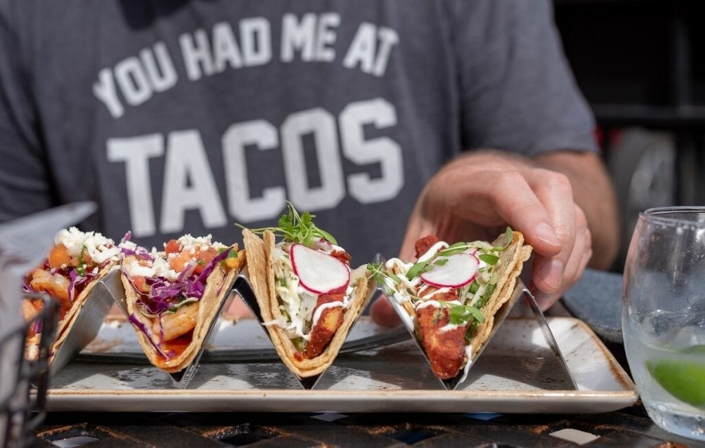Man wearing grey tshirt that says: You had me at Tacos - in the foreground metal taco holder tray with 4 tacos
