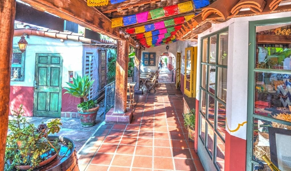 store fronts with terracotta tile walkway, white walls, wood covered path and colorful paper garlands