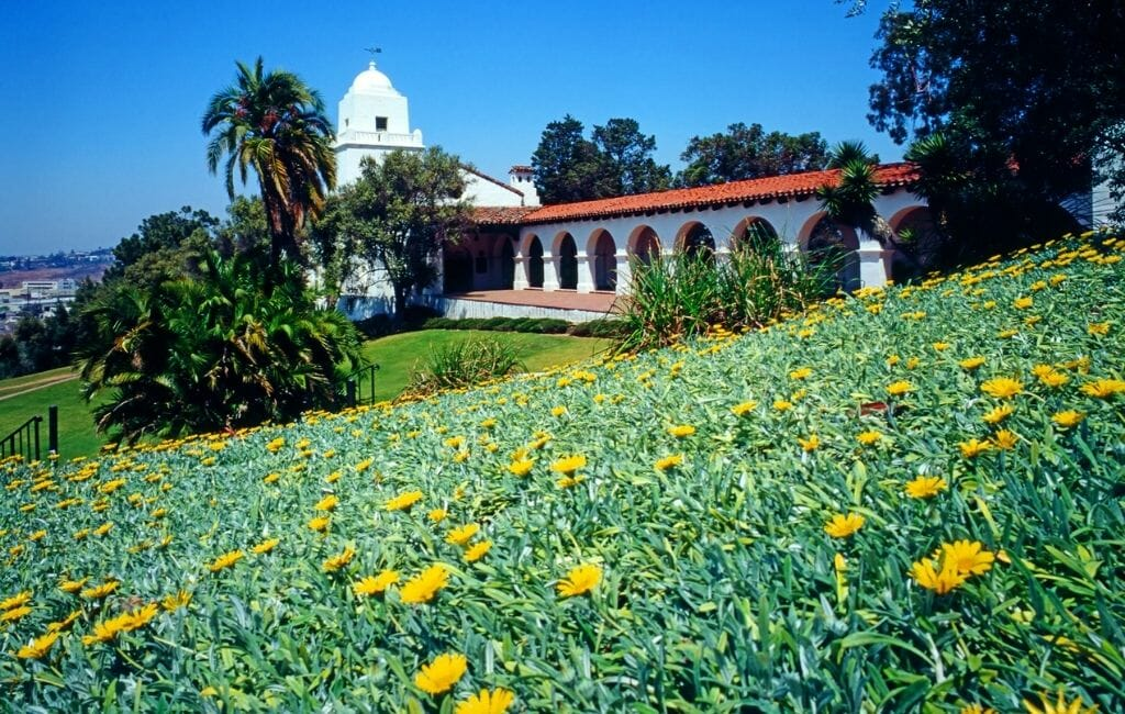 White building that looks like a mission with arched covered walkways and bell tower - JUNÍPERO SERRA MUSEUM Old Town San Diego California