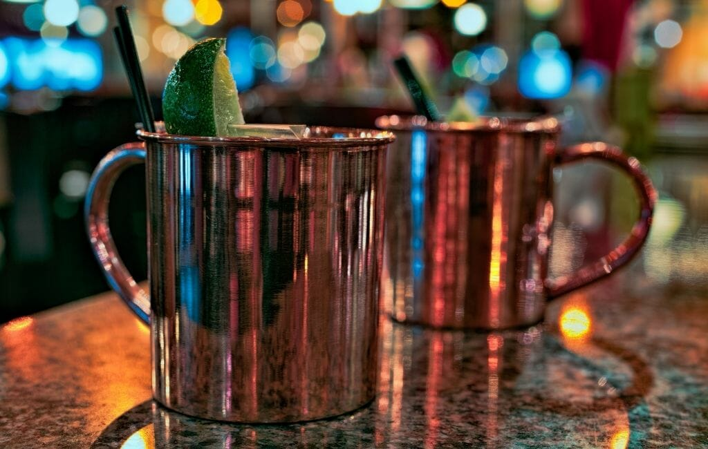 Closeup of two copper cups with cocktails
