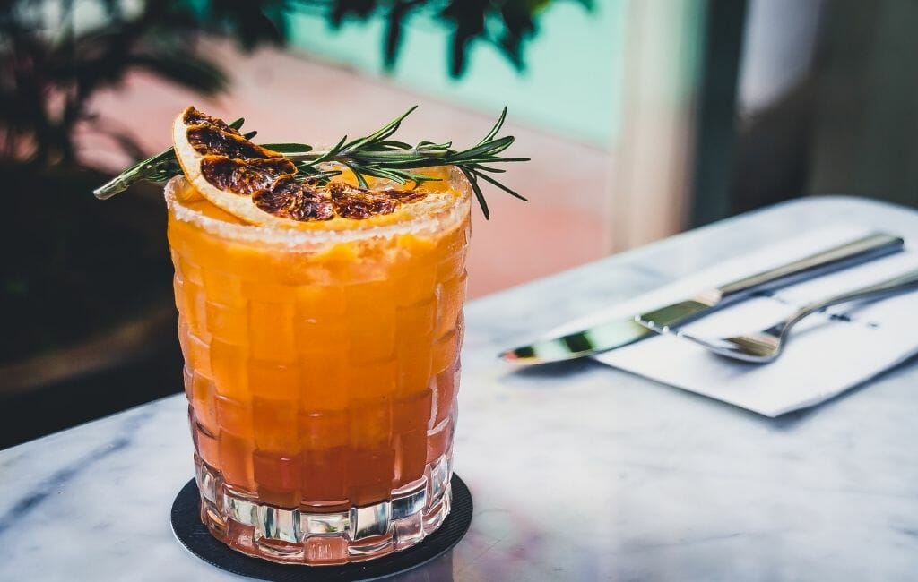 Mexican Mezcal coctail in a glass with rosemary and blood orange