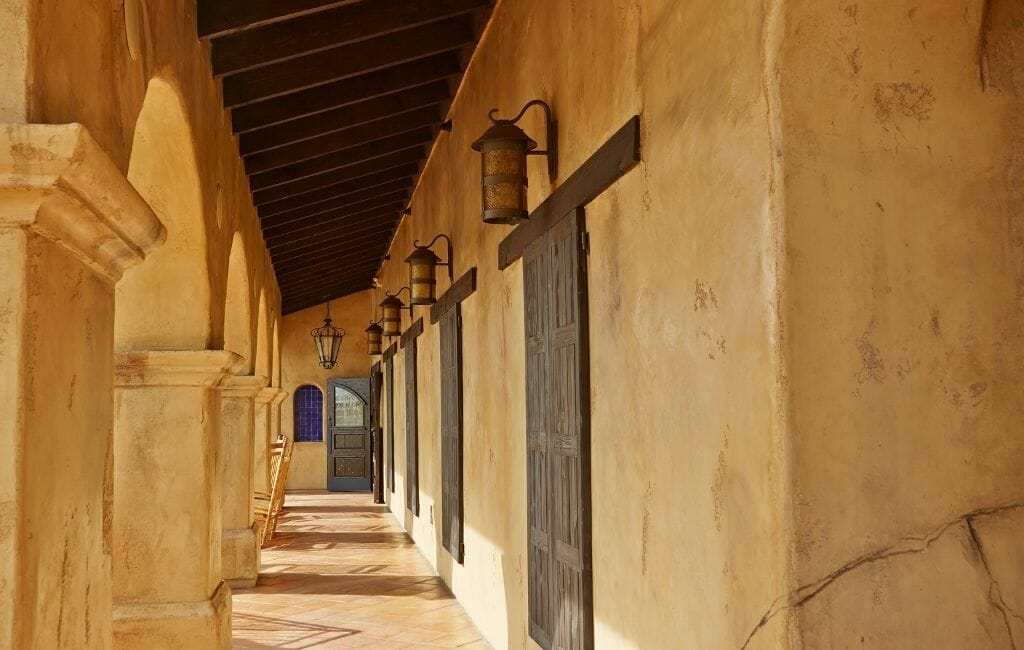 Historic military building with tan colored walls, dark wood doors along an arched covered walk way at the Mormon Battalion Old Town San Diego California
