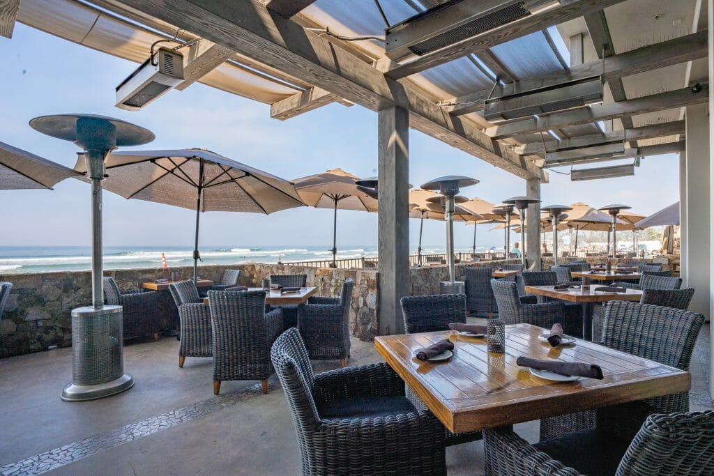 outdoor patio with with white umbrellas and heaters overlooking the beach at Pacific Coast Grill