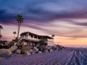 View of two story building right on the beach during sunset photographed from the beach - home to Pacific Coast Grill