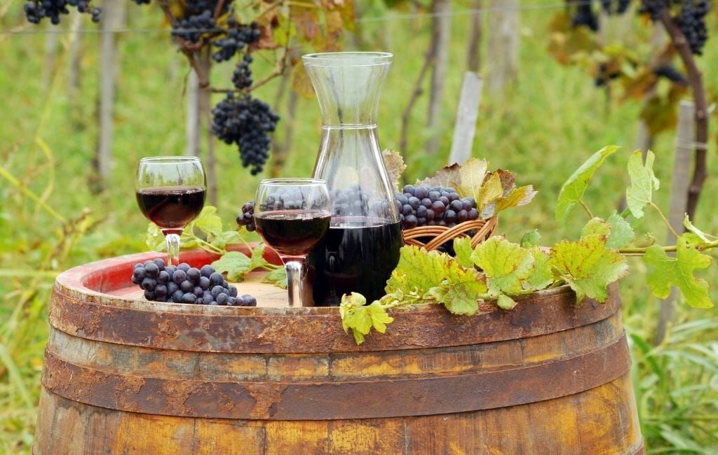 Old rustic wine barrel in a vineyard with wine glasses and bottles and grapes on top - Temecula Red Wines