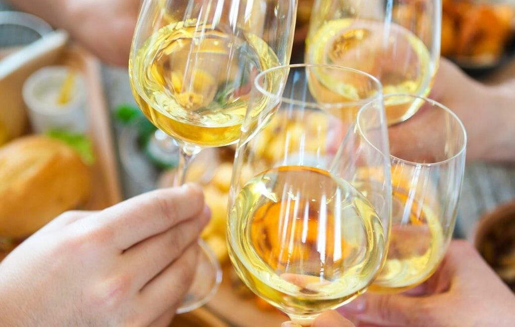 4 white wine glasses with hands toasting with each other