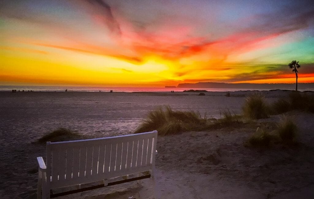 Colorful sunset on Coronado Island with white bench and sand in the foreground