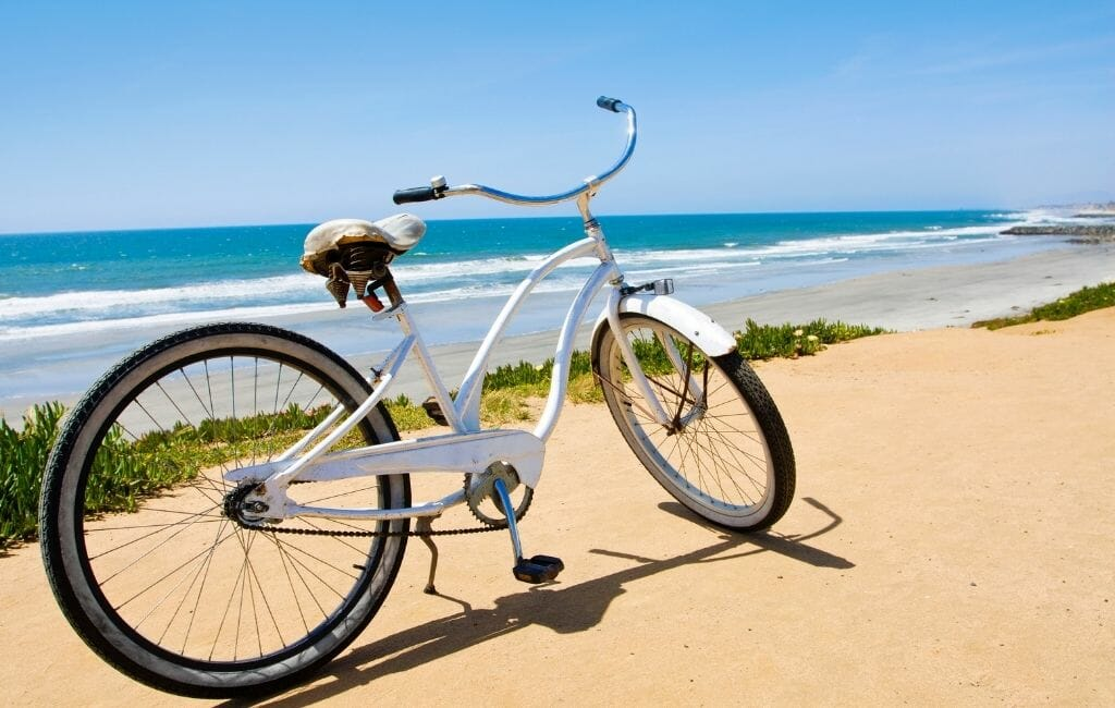 White beach cruiser bike on a sandy path overlooking the ocean