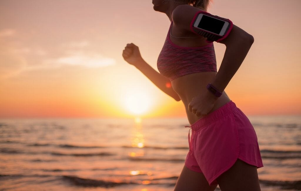 Woman in pink shorts jogging on the beach during sunset