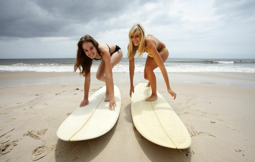 Two young women practicing surfing on surfboards on the sand