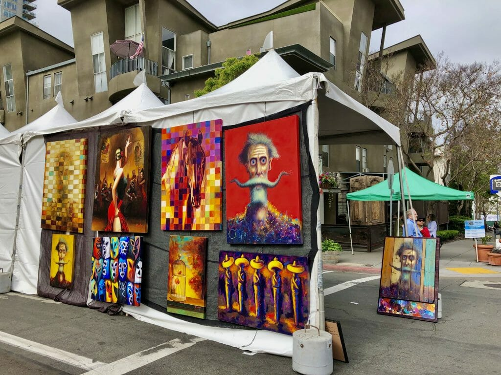 White market booths with colorful modern art  hung on the outside walls at Art Walk Little Italy