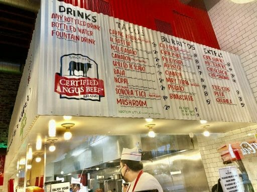 white menu with red writing over counter at The Taco Stand Taco shop in Downtown San Diego
