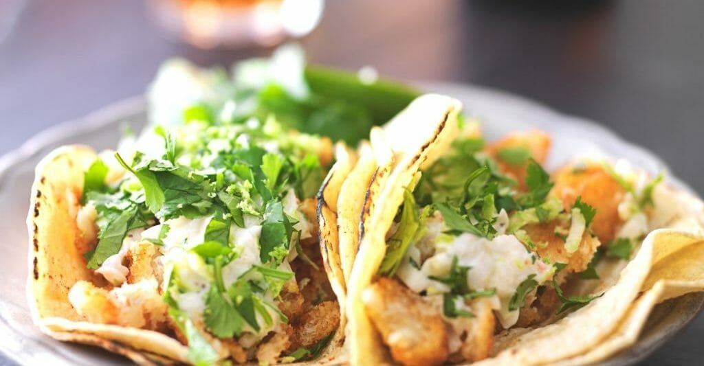 two fish tacos on a plate with a drink blurry in the background - Fish Tacos Petco Park San Diego