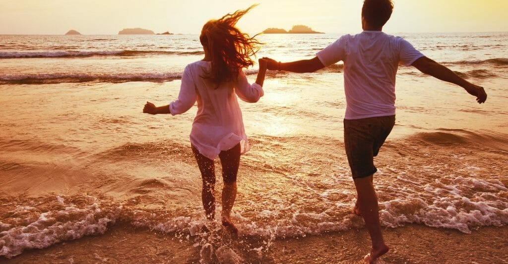 young couple running into the shallow water on the beach during sunset while holding hands