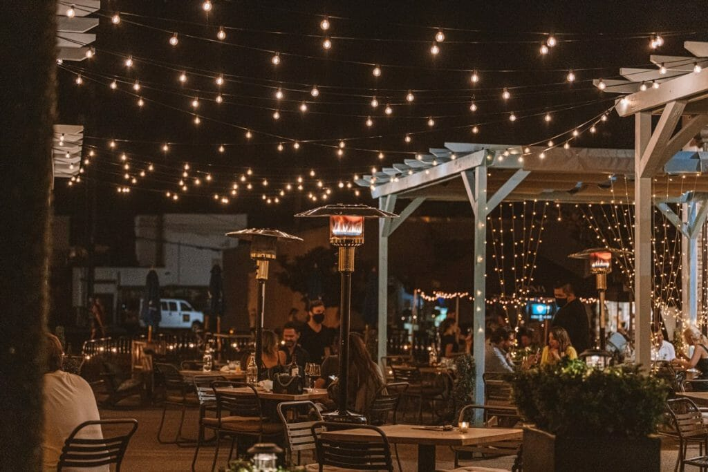 Outdoor patio at Herringbone La Jolla with tables, white pergolas and string lights at night