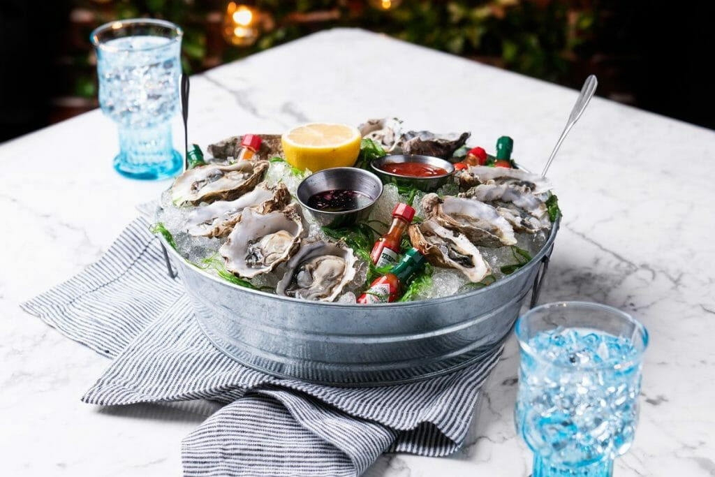 metal tub with ice and oysters on top on a white table with two blue water glasses