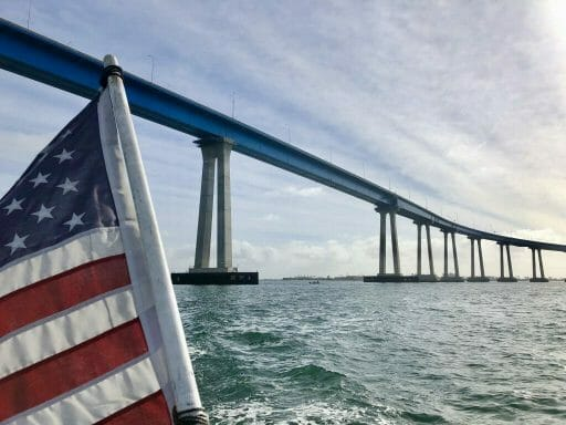 View from back of the boat with american flag on the left and looking up at the tall pilars of the curved Coronado Bay Bridge