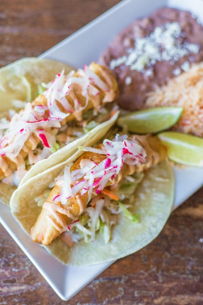 2 Fish Tacos with a side of rice and refried beans on a rectangular white plate